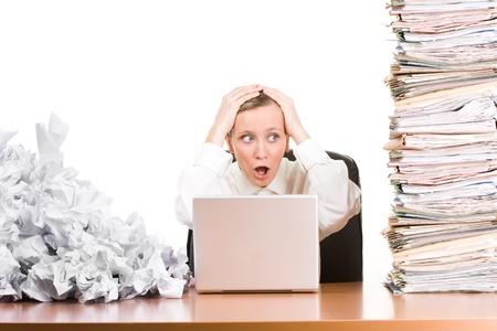 in a pile: Una mujer sentada en su escritorio con documentos apilados.