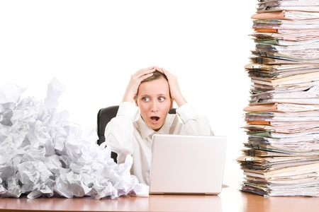wadded: Stressed businesswoman with stack of paperwork, pile of crumpled papers and a laptop computer.