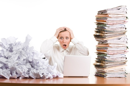 arquivos: A young woman stressed at work with a pile of paperwork.