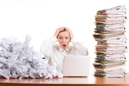 Een jonge vrouw benadrukt op het werk met een stapel papierwerk. Stockfoto