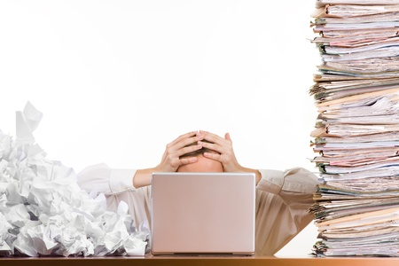 A stressed person holding his head behind a laptop surrounded by a pile of files and papers, Stock Photo