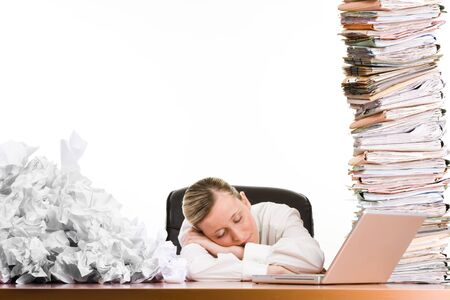 A woman sleeping on a desk surrounded by a stack of file folders, paper trash and a laptop computer. Stock Photo - 9570919