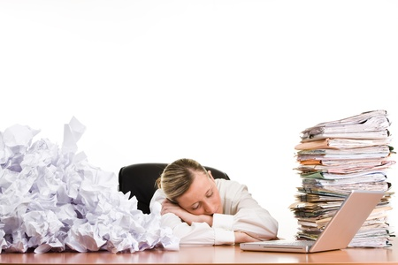 A woman sleeping on a desk surrounded by a stack of file folders, paper trash and a laptop computer. Stock Photo - 9570901