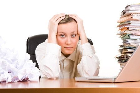 A stressed female executive with her head in her hands, sitting at her desk covered a pile of papers and stack of files. photo
