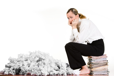 A woman sitting on a stack of files next to crumpled paper.  photo
