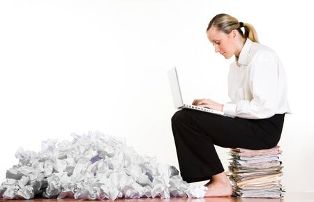 A woman using a laptop computer, sitting on a stack of file folders and paperwork beside a pile of crumpled paper.  White background Stock Photo - 9575064