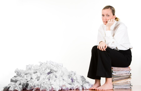 stressed out: Businesswoman with pile of crumpled papers sitting on a stack of paperwork.