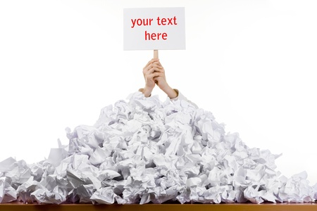 screwed: Office worker with sign buried in pile of screwed up papers, white studio background Stock Photo