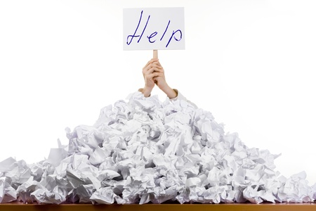 paperwork: Person under crumpled pile of papers with hand holding a help sign isolated against a white background. Stock Photo