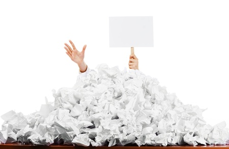 Office worker with blank sign buried in pile of screwed up papers, white studio background. Stock Photo