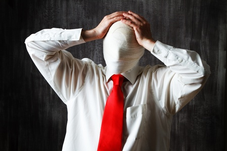 obscured: Half body portrait of businessman with face obscured by bandages, dark background.