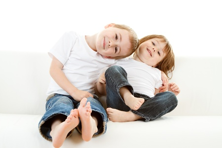 Happy young preschool barefoot boy and girl relaxing on settee or sofa, white background.