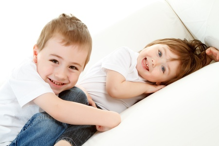 kiddies: Happy preschool boy and baby sister relaxing on white background. Stock Photo