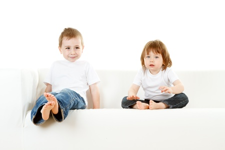 Cute preschool boy and girl on white settee or sofa, studio background. photo