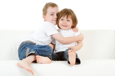 playmates: Dos j�venes hermanos juguetonamente abrazos.  Fondo blanco