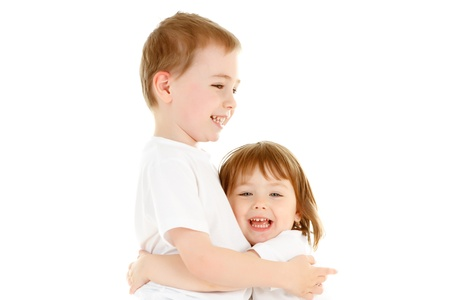 Two beautiful Caucasian children, a boy and a girl, hugging each other with happy smiling facial expression. Image isolated on white studio background. photo
