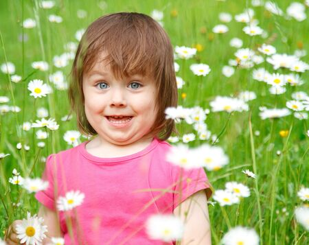 Closeup of a smiling little girl with bright blue eyes, in a field of white and yellow flowers. photo