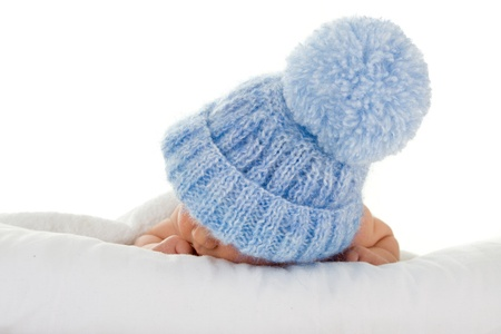 Sleeping infant wearing a blue knit hat with a pompom.