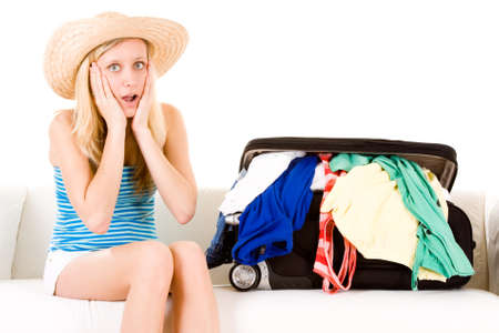 unpacked: A woman looking at her unpacked suitcase, on her holiday. Stock Photo