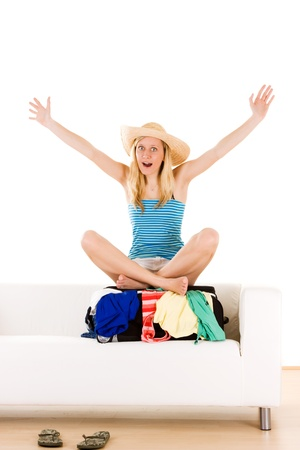holidaymaker: Happy teenage holidaymaker sat on shut overflowing suitcase, white background.