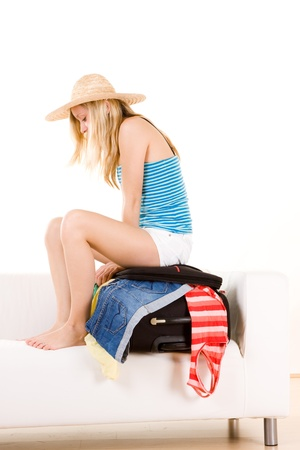 holidaymaker: Teenager holidaymaker sat on overflowing suitcase, white background.