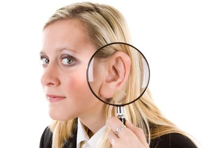 �couter: Une femme avec une loupe � c�t� de son oreille. Veuillez �couter.  Banque d'images