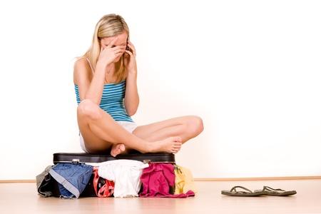 over packed: Ha sottolineato adolescente seduto sulla cima di sopra valigia imballato, sfondo bianco.