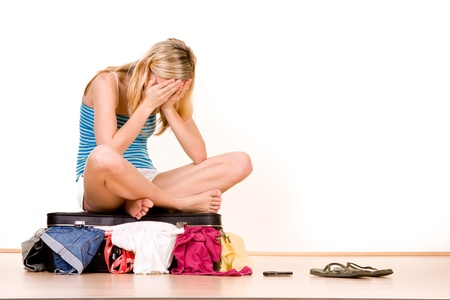 downhearted: Stressed teenager sat on top of over packed suitcase, white background.