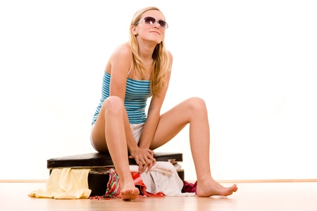 packing suitcase: Girl wearing sunglasses sitting on a full suitcase to close it.