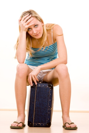 flip flops: Closeup of stressed young blond woman sat on suitcase, white background.