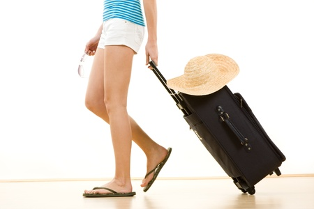 flops: Side view of female holidaymaker in flip flops pulling suitcase with sun hat on top, white background. Stock Photo