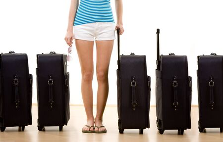 holidaymaker: Closeup of female holidaymaker with row of five packed suitcases, white background. Stock Photo