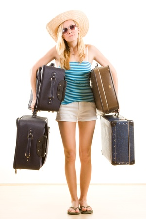 flops: Closeup of young female holidaymaker in sunglasses and floppy hat carrying suitcases, isolated on white background.
