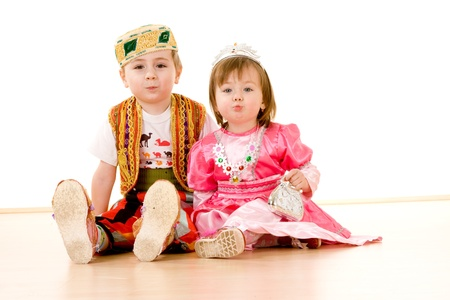 colorful dress: Closeup of young brother and sister in fancy dress party costumes, white background. Stock Photo