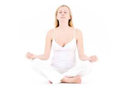 Blond haired teenager meditating in yoga pose, isolated on white background. photo