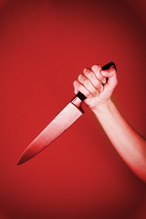stabs: A red background with a hand coming through holding a knife.  Stock Photo