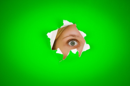 nosey: Closeup of persons eye peeping through tear in green background.