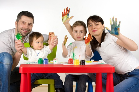 childern: Happy parents with thier childern enjoy painting with assorted colours on hands Stock Photo