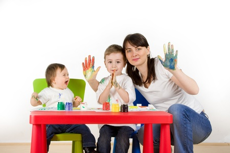 childern: Mother with her childern enjoy painting with assorted colours on hands