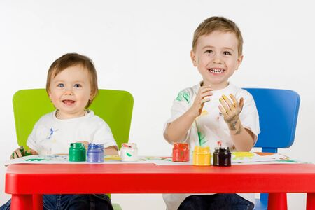 smiling little boy and girl enjoy painting with assorted colours photo