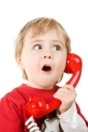 Little boy holding a red telephone receiver.  Isolated against a white background. photo