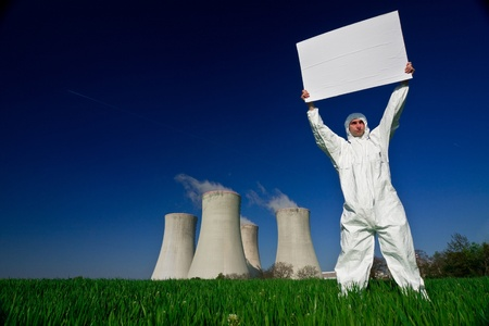 A worker in a uniform standing with a blank banner in front of a nuclear power plant. photo