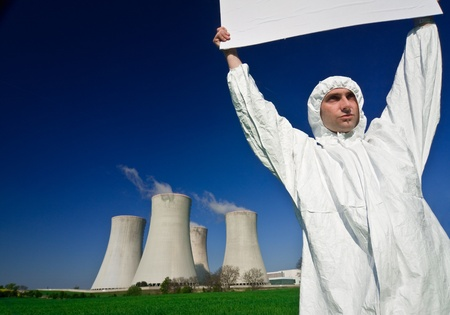 metaphorical: A metaphorical image of a uniformed man with a banner protesting in front of a nuclear power plant, for environment protection.