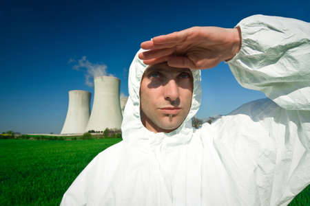 Man in white jumpsuit shielding the sun at a power station. Stock Photo - 9712414