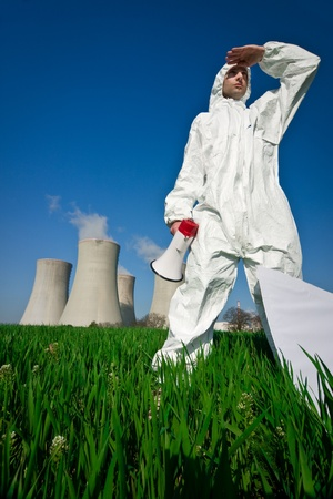 nuke plant: Protester in protective clothing with a megaphone, standing in a flowering field in the foreground of a nuclear power plant. Stock Photo