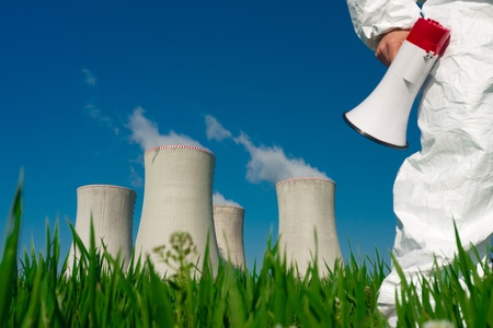 nuke plant: Manifestante en ropa protectora con un meg�fono, en un campo de las torres de refrigeraci�n de una planta de energ�a nuclear.  S�lo la pierna derecha y el meg�fono de mano derecha son visibles de la manifestante. Foto de archivo