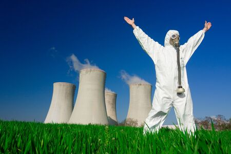 Man wearing protective suit and gas mask standing in front of nuclear power plants. photo