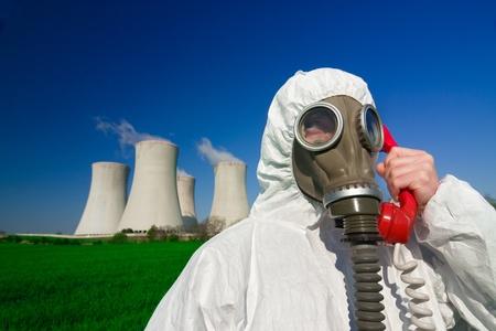 hazmat: Una vista di un uomo che indossa una maschera di respirazione e una tuta ignifuga, in piedi davanti a una centrale nucleare e parlando un telefono rosso.