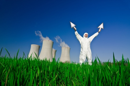 Man wearing protective suit standing in front of a nuclear power plant holding arrows pointing upwards. photo
