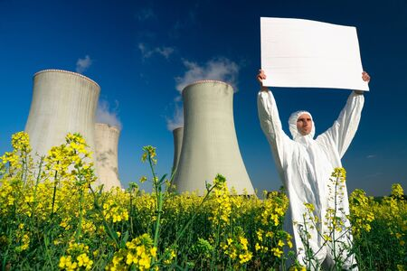 A view of a man in a protective suit, holding a blank sign in front of a nuclear power plant. photo